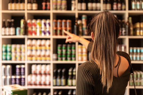 A young woman pointing at canned beers in a liquor shop and choosing some.