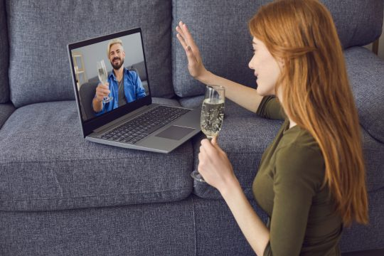 Man and woman drinking wine as they video chat on the computer