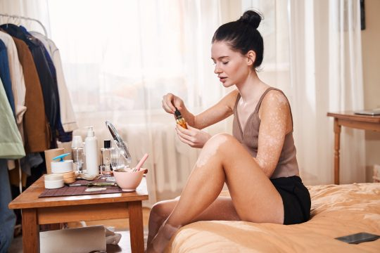 Woman using a serum in front of her mirror