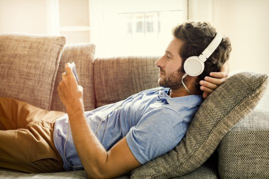 Man listening to a mix tape on the couch