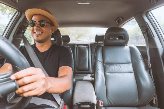 Man driving, happily with a cool hat sunglasses on